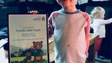 Little 'superhero' Freddie Taylor with his certificate for bravery from the ambulance service.