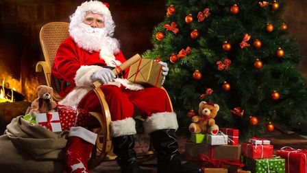 Santa Claus sitting in front of fireplace near Christmas tree with a bag full of presents and a wish