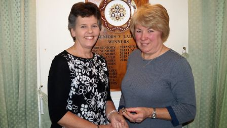Sidmouth Golf Club's outgoing lady captain Maria Clapp (right) hands over the brooch to the new lady