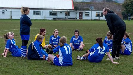 Ottery ladies coach Mike Ringer conducts his half-time chat on the pitch at Greenway Lane