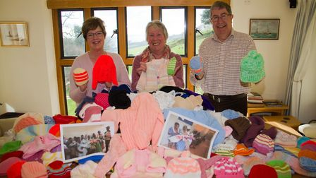 Duncan and Rosalind Watts with Jean Bridgeman with some of the knitted donations for the Uganda proj