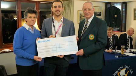 Sidmouth captain's Maria Clapp (left) and Richard Powell present a cheque to Jordan Anderson (centre