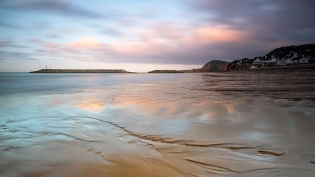 Looking west at low tide along the beach at Sidmouth just after a summer sunrise. Picture: Paul Newm