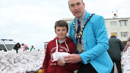 Councillor Stuart Hughes hands out the first of the hot cross buns to Jack Mesher who was first in t
