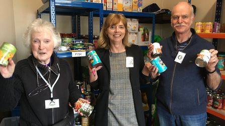 Foodbank staff fill shelves with supplies