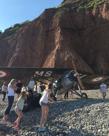 A vintage light aircraft makes an emergency landing on Sidmouth beach on a packed bank holiday weeke