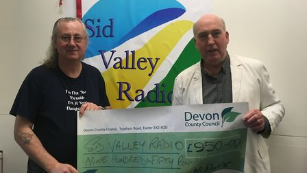 Bob Weeks of Sid Valley Radio accepts a cheque of £950 from Councillor Stuart Hughes towards the pri