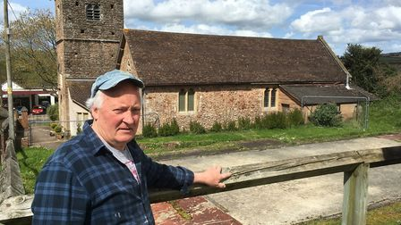 Dan Smith. church volunteer, with the space left by the church hall fire