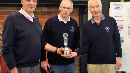 Sidmouth seniors captain Tony Stoyle (centre) presenting the home team trophy to H Thompson and Grah