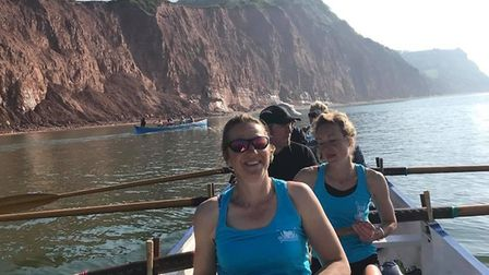 Sidmouth Gig Club crews passing collapsing cliffs as rowers leave Sidmouth