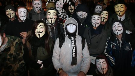 Protestors demonstrate in Guy Fawkes masks. Photograph: Niall Carson/PA.