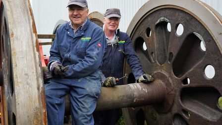 """Volunteers Ray Evans and Roger Hughes cleaning a set of Sidmouth's 6'2"""" diameter driving wheels."""