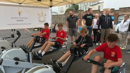 Sidmouth Surf Lifesaving Club members rowing to fundraise money on the seafront.