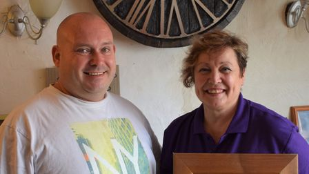 Mike and Jacqui Down of the Volunteer Inn with their new clock which has been made out of the tar ba