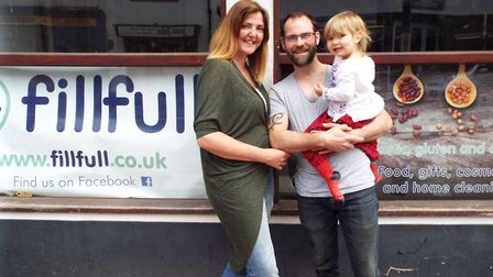 Alice Bardwell and Dan Price with their daughter Matilda outside their shop FillFull which they are