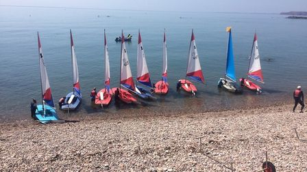 Sidmouth Sailing Club members in their dinghies waiting to head off onto the open sea.