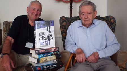 RVS Volunteer David Evans with reader Bill Lovell and some of the books he has taken out and deliver