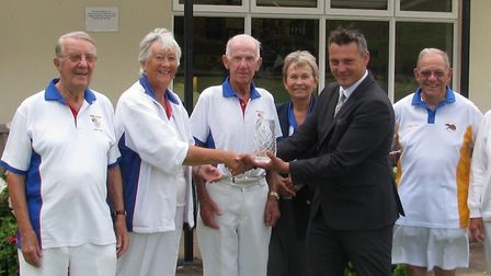 Redferns' Lee Maddicks presenting the trophy to the winning team of Budleigh Salterton flanked by cl