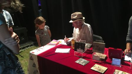 Roger McGough signs a book for Eleanor, 8, from Sidmouth
