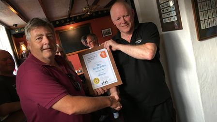 A representative from CAMRA presents Vince Palmer, landlord of the London Inn in Ottery, with an awa