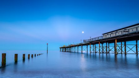 The Grand Pier looks resplendent at dusk, bathed in blue and lit up by a summer full moon. Built by