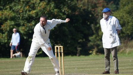 David Thayre bowls for Tipton in the game against Kays watched by umpire Peter Philbrick. Picture PH