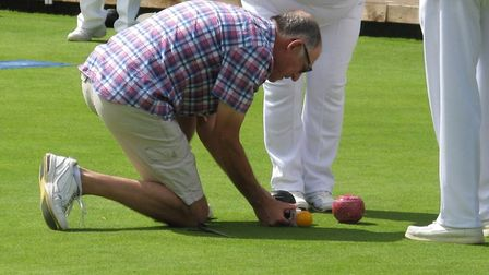 Acting umpire Leighton Burston uses the tape to determine the winning wood during the Ottery St Mary