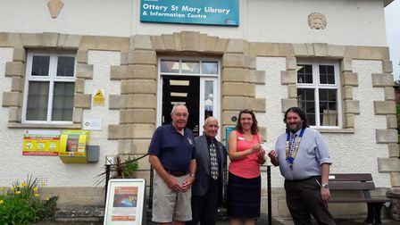 Jamie Love, President of the Honiton Lions Club presents a cheque to Xanthe Waite, Library Supervis