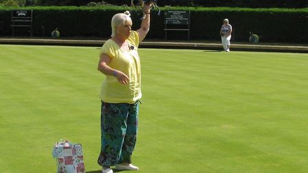 Ottery St Mary Bowls Club captain Terri Ward raises aloft the spider that was the subject of a compe