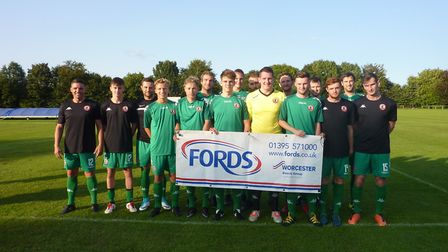 Sidmouth Town players with a banner following the club's announcement of a major sponsorship agreeme