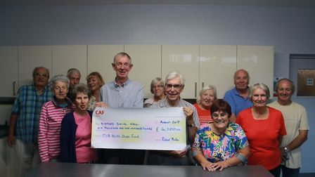 Alan Clarke of the SVA handing over a cheque for £6,100 to members of the Sidford Hall committee to