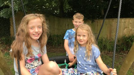 Anna, Georgie and Benjy Barrett-Miles on the new tyre swing at West Hill play park. Picture: Clariss
