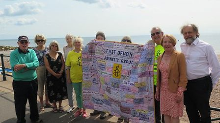 Members of East Devon Amnesty Group with the quilt which will go to Parliament to raise awareness of