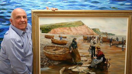 Artist Peter Goodhall with his painting of fisher folk on Sidmouth beach. Picture: Contributed