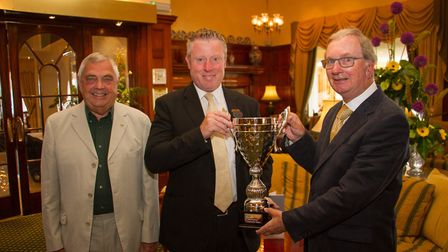 Duncan Henshaw of the Victoria Hotel hands over a new cup for this years swimaton to John Kinch and