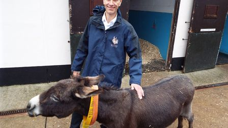 The Donkey Sanctuary's visitor engagement manager John Crouch with one of the 220 housed donkeys. Pi
