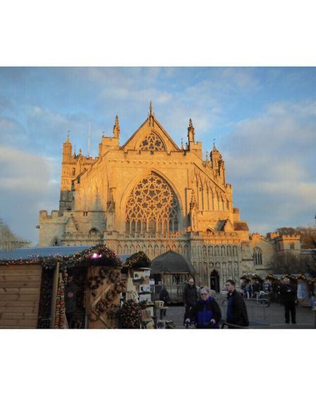 Exeter Cathedral in the golden glow of the late evening sun surrounded by the Christmas market stall