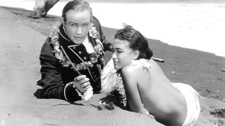 Marlon Brando in a military uniform with a lei around his neck and relaxing with topless, Tarita on