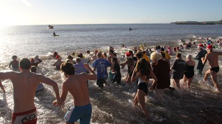 Sidmouth Boxing Day swimmers head into the waves on Thursday. Photo by Simon Horn. Ref shs 8555-52-1