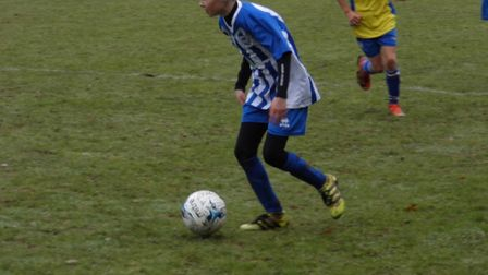 Fin Giles in action for Ottery St Mary U13s during their meeting with table-topping Brixington Blues