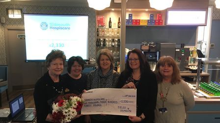 Company director Becky Murphy presents a cheque to Gill Ryall of Hospiscare (cebtre) with Fields sta