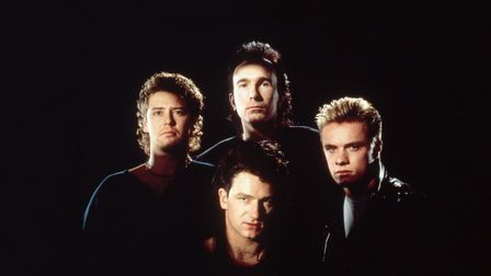 Adam Clayton (far left), The Edge (back), Bono (front) and Larry Mullen, Jr. (far right) form the rock band U2.