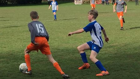 Sam Gleeson of Ottery St Mary U13s presses an Alphington opponent during the 2-2 draw between the te