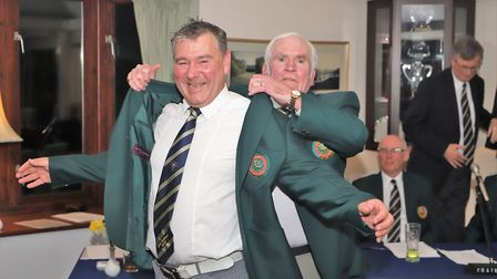 The outgoing captain, Colin Macklin, helps new captain Neil Holland into his club blazer. Picture SG