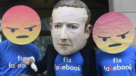 A Mark Zuckerberg figure with people in angry emoji masks outside Portcullis House in Westminster ah