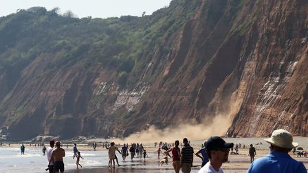 The fall brought quite a crowd as dust flies up as the cliff crumbles at Jacobs Ladder. Picture: Sim