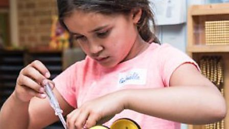 A youngster tries her hand at one of the many Repair Cafes in the world.