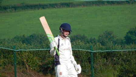 Ottery St Mary 2nd Xi skipper Eddie Rudolph raises his bat after reaching a half century in his side