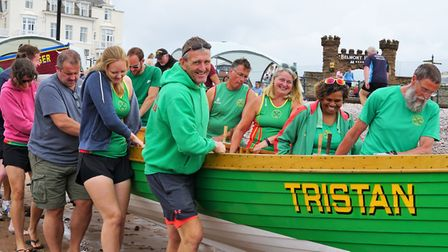 Sidmouth Gig Club crew getting a boat down to the water ahead of racing at the Sidmouth regatta. Pic