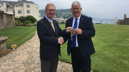 Sidmouth Rotary Club's John Kinch hands over the presidental chain to Keith Walton at the Victoria H